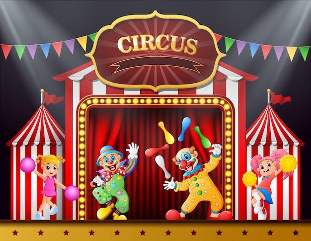 Espectáculo de circo con payasos y animadoras en el escenario.