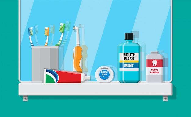 Espejo de baño y herramientas de limpieza dental.