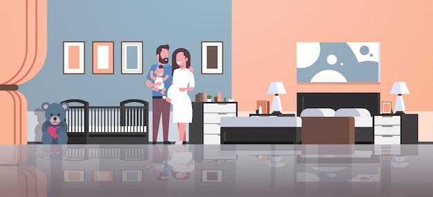Esposo con esposa embarazada con hijo recién nacido de pie cerca de la cuna