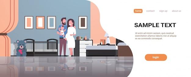 Esposo con esposa embarazada sosteniendo a su hijo recién nacido parado cerca de la página de inicio
