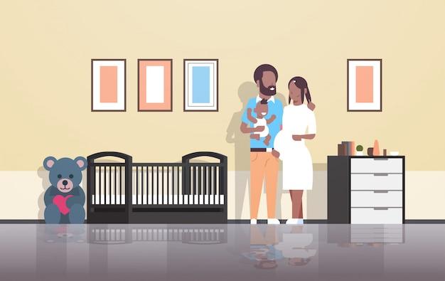 Esposo con esposa embarazada sosteniendo a su hijo recién nacido de pie cerca de la familia de la cuna