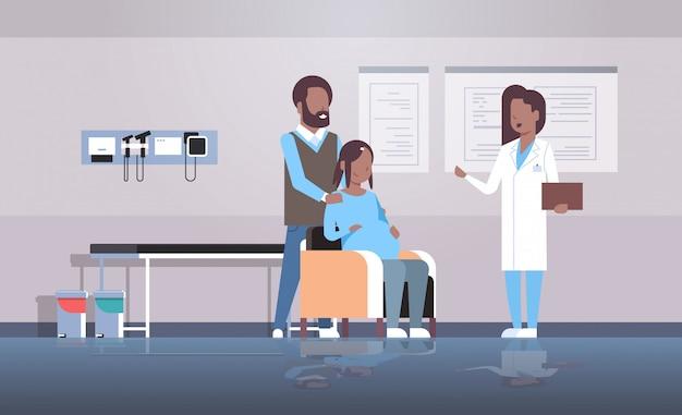 Esposo con esposa médico visitante ginecólogo realizando consulta de ginecología del embarazo