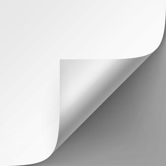 Esquina rizada de papel blanco con sombra de cerca sobre fondo gris