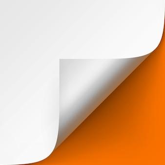 Esquina rizada de papel blanco con sombra de cerca sobre fondo naranja