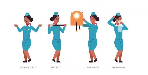 Establecer azafata explicando instrucciones con chaleco salvavidas, cinturón de seguridad, salida de emergencia y máscara de oxígeno, azafata afroamericana en concepto de demostración de seguridad uniforme de longitud completa horizontal