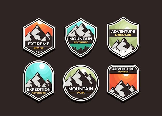 Establecer el logotipo y las insignias de la montaña. un logotipo versátil para su negocio. ilustración en una oscuridad