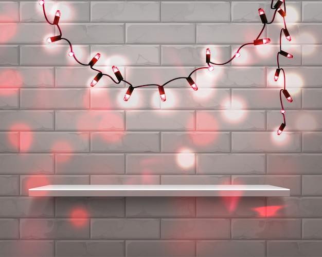 Estante blanco realista en el frente con guirnaldas de luces rojas navideñas sobre fondo de pared de ladrillo con superposición de brillo