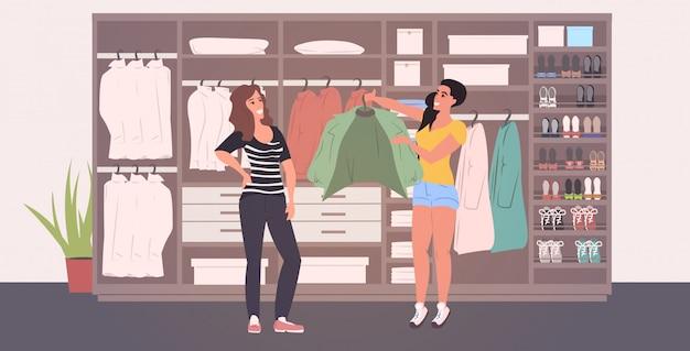 Estilista de moda ayudando a la mujer a elegir atuendo en el vestuario con diferentes zapatos y ropa con estilo moderno vestidor interior horizontal completo