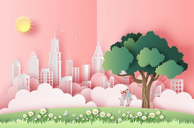 Estilo de arte de papel de linda pareja sentada en un columpio debajo de un árbol en una gran ciudad.