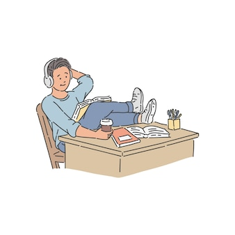 Estudiante en auriculares con taza de café sentado con las piernas en la mesa y libro de lectura