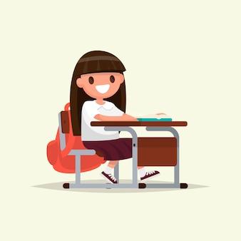 Estudiante de escuela primaria. la colegiala se sienta en un pupitre.