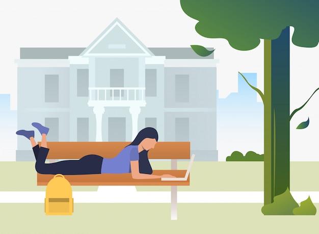Estudiante estudiando, usando una computadora portátil y acostado en un banco en el parque del campus
