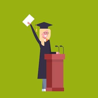 Estudiante de girl happy in graduation cap y bata de pie en el tribune hold diploma