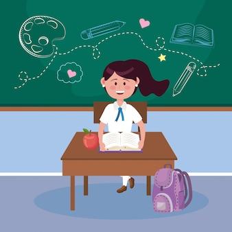 Estudiante de niña con fruta de manzana y libro en el escritorio