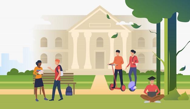 Estudiantes caminando y conversando en el parque del campus