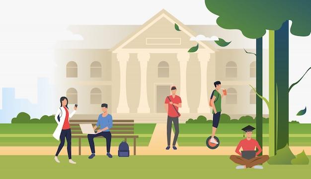 Estudiantes caminando y relajándose en el parque del campus
