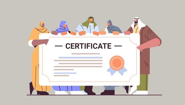 Estudiantes graduados árabes de pie juntos cerca de graduados árabes certificados celebrando el título de diploma académico