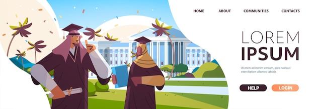 Estudiantes graduados árabes de pie juntos cerca de graduados de edificios universitarios celebrando el título de diploma académico