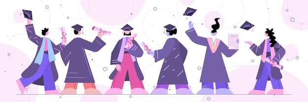 Los estudiantes graduados de pie juntos los graduados celebrando el diploma académico grado educación certificado universitario concepto horizontal de longitud completa