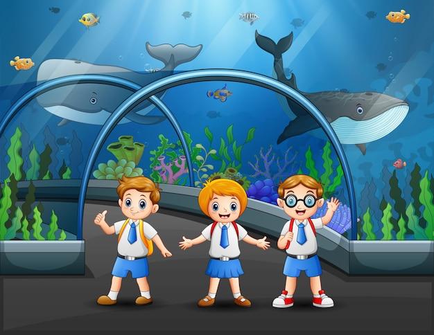 Estudiantes en uniforme visitando la ilustración del acuario