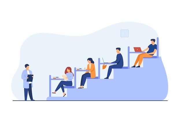 Estudiantes universitarios sentados en escritorios en el aula y escuchando al maestro.
