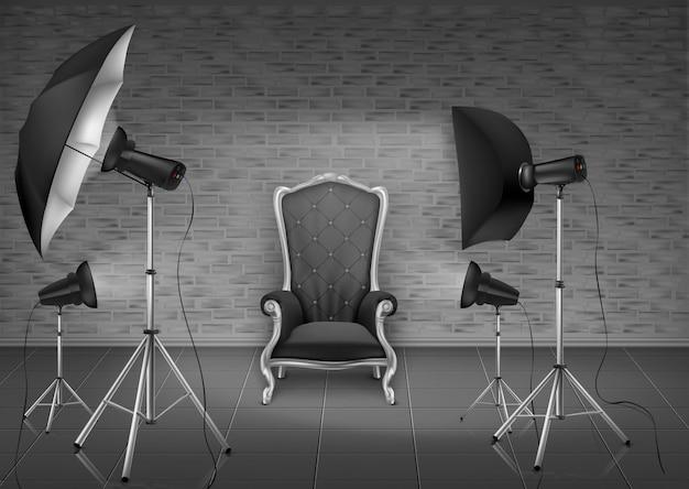 Estudio fotográfico con sillón vacío y pared de ladrillo gris, lámparas, difusor de paraguas.