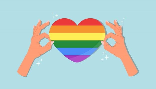 Etiqueta engomada del corazón del orgullo en las manos.