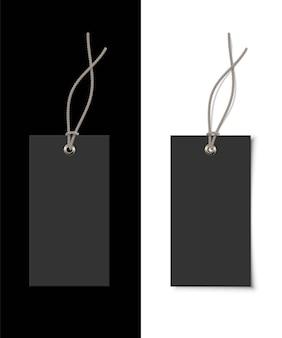Etiqueta de ropa de papel negra vacía con remache metálico y cinta gris sobre fondo blanco y negro.
