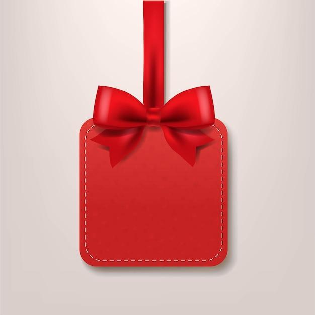 Etiqueta de venta de papel rojo con cinta de seda roja.