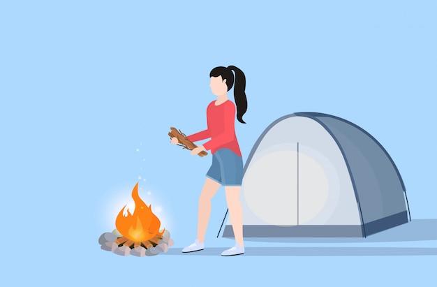 Excursionista de mujer haciendo fuego chica sosteniendo leña para fogata senderismo camping concepto viajero en caminata ilustración de vector plano de longitud completa horizontal
