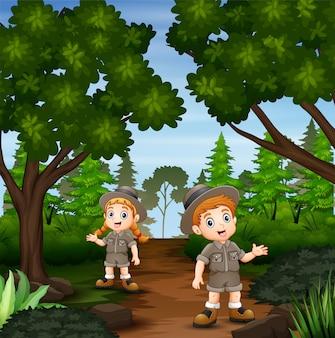 El explorador niño y niña en el bosque