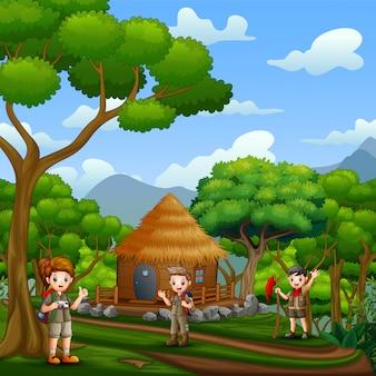 Los exploradores frente a una cabaña de madera en el bosque