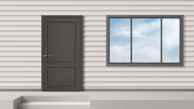 Fachada de la casa con puerta gris, ventana, revestimiento