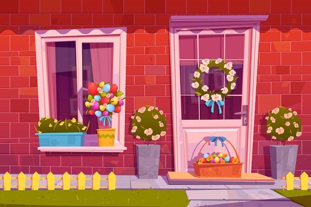Fachada de la casa rural decorada para las vacaciones de pascua con huevos en canasta y corona de flores o ramo