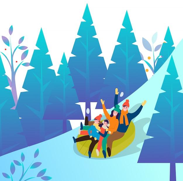 Familia divirtiéndose en el bosque de invierno bajando