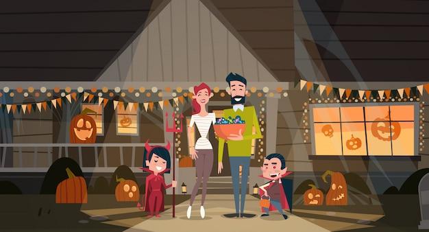 Familia feliz celebrar halloween los padres y los niños usan disfraces de vampiros decoración concepto de fiesta de terror