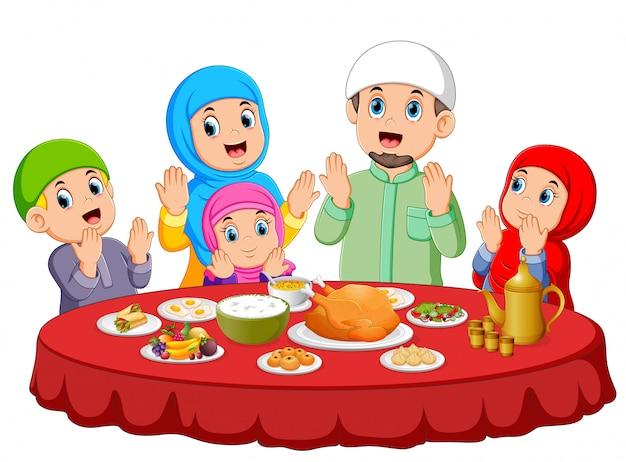 Una familia feliz está orando por comer la comida en el ied mubarak
