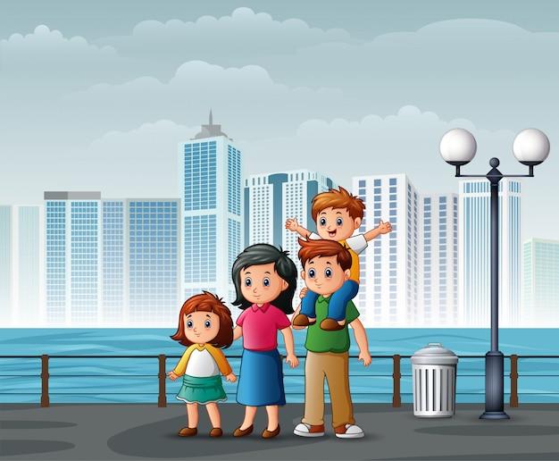 Familia feliz de pie en la orilla del río a través de las ciudades