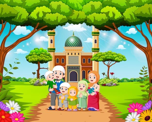 La familia feliz posa frente a la hermosa mezquita.