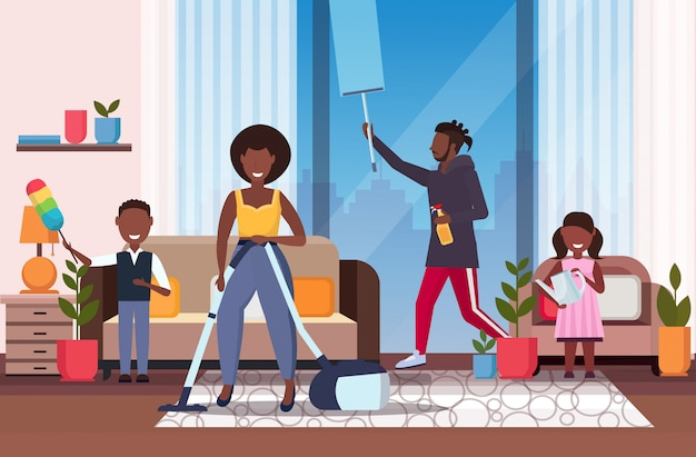 Familia haciendo tareas domésticas afroamericano padre limpiando ventana madre usando aspiradora niños desempolvando y regando plantas limpieza concepto de limpieza sala de estar interior de cuerpo entero horizontal