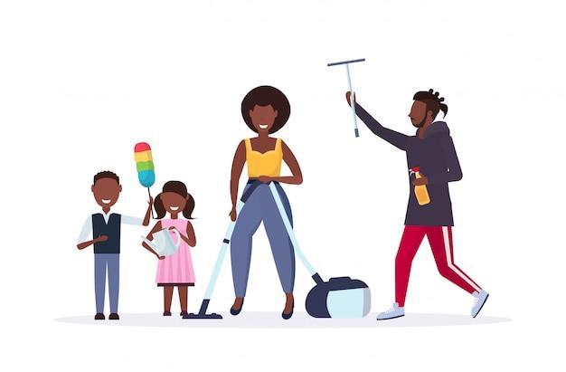 Familia haciendo tareas domésticas juntos afroamericano padre limpiando ventana de cristal madre usando aspiradora niños polvo limpieza concepto de limpieza fondo blanco horizontal de longitud completa