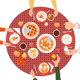 Familia en la mesa. día de gracias. pastel de calabaza y pastel de manzana, beber té