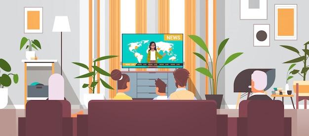 Familia multigeneración viendo televisión, programa de noticias diarias, pasar tiempo juntos en el interior de la sala