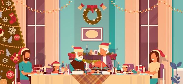 Familia de múltiples generaciones celebrando las vacaciones de año nuevo personas sentadas a la mesa concepto de cena tradicional decorado árbol de navidad sala de estar interior plano horizontal