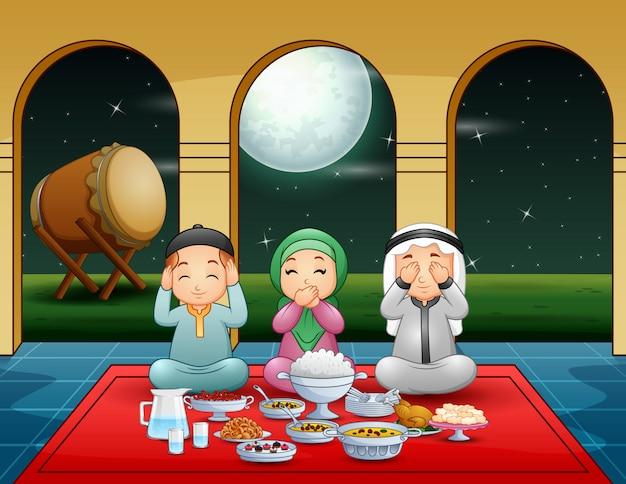 Familia musulmana rezan juntos antes de la pausa del ayuno