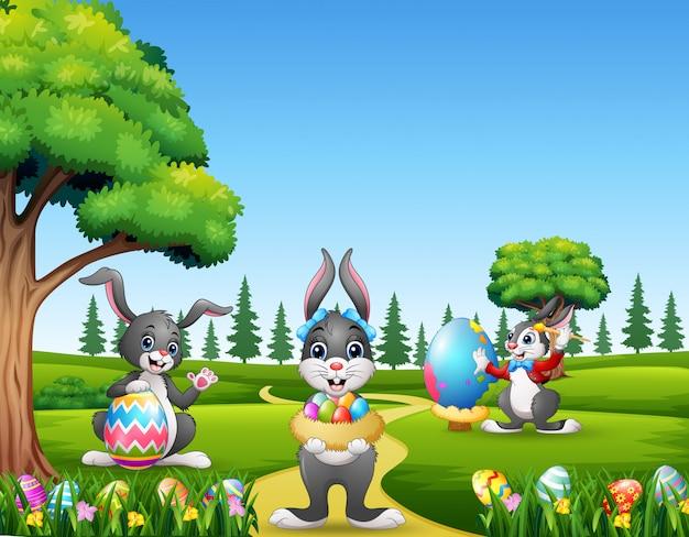 Felices conejitos de pascua sosteniendo y pintando huevos