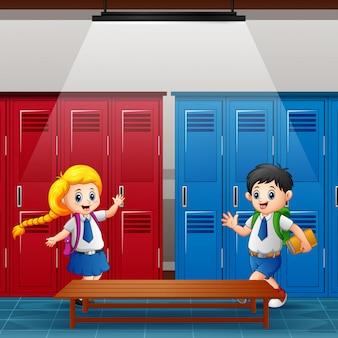 Felices niños de la escuela se reúnen en el vestuario.