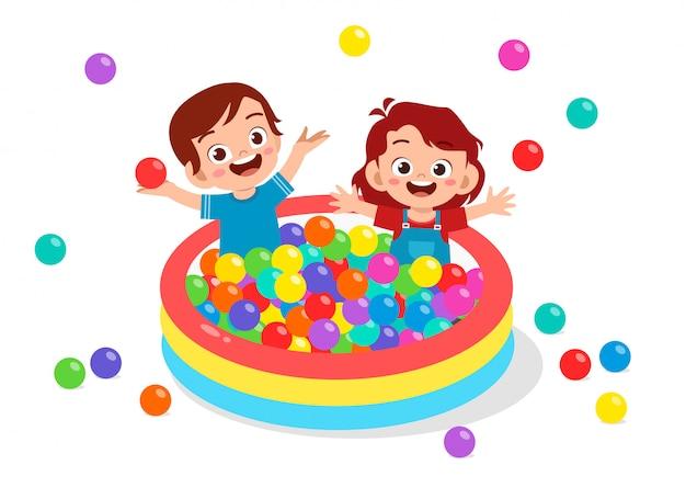Felices los niños lindos juegan piscina de baño de pelota