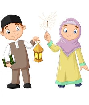 Felices niños musulmanes con libro de corán y linterna de ramadán