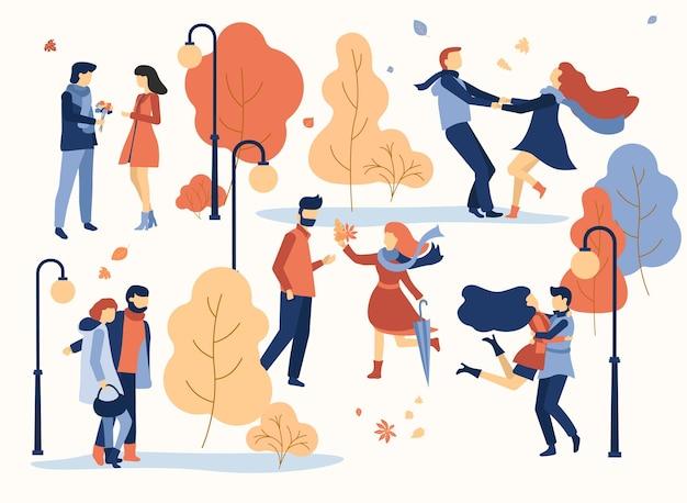 Felices parejas enamoradas se encuentran y caminando en el parque otoño dorado